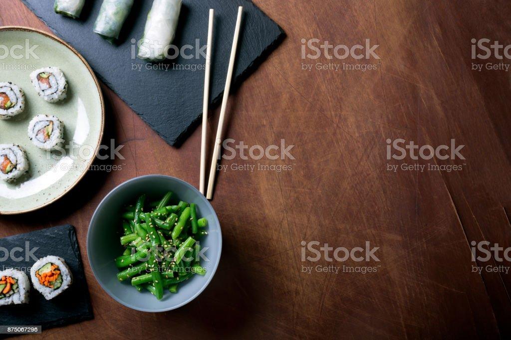 Japanse sushi en groene bonen op een donkere houten achtergrond - Royalty-free Alleen volwassenen Stockfoto