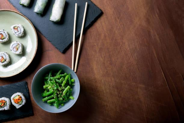日本の寿司と暗い背景の木の緑の豆 - 和食 ストックフォトと画像