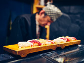 A Japanese sushi chef serving customers in a small sushi shop in Tokyo, Japan.