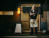 A mature aged Japanese sushi chef standing in a front of his shop at night.