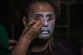 日本の太鼓アーティストの男は、悪魔のマスクの形で顔に化粧を置き、肖像画をクローズアップ