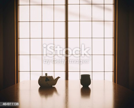 A Japanese teapot sits silhouetted at a table.