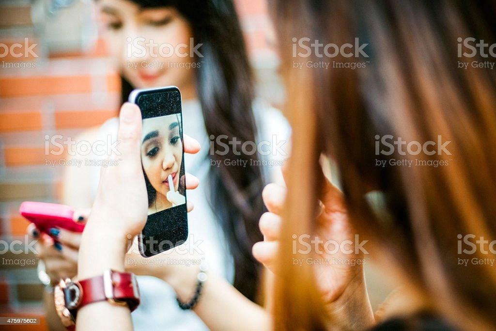 Japanese Teenage Girls using Smartphone as Vanity Mirror stock photo