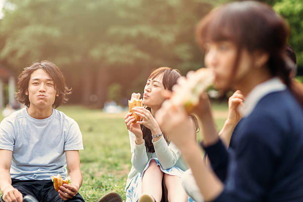 Japanese teenager eating outside Japanese teenagers eating some fast food outside in the park. There is a lovely sunny day. The food seem delicious and they seem very happy. female sandwich stock pictures, royalty-free photos & images