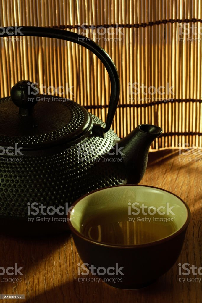 Japanese Tetsubin kettle with a cup of green tea stock photo