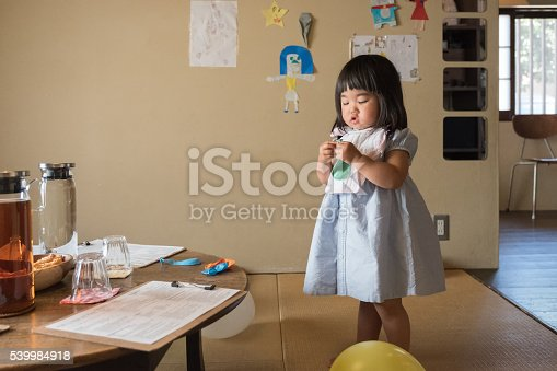 istock Japanese Toddler Girl Examining Balloon, Getting Ready for Birthday Party 539984918
