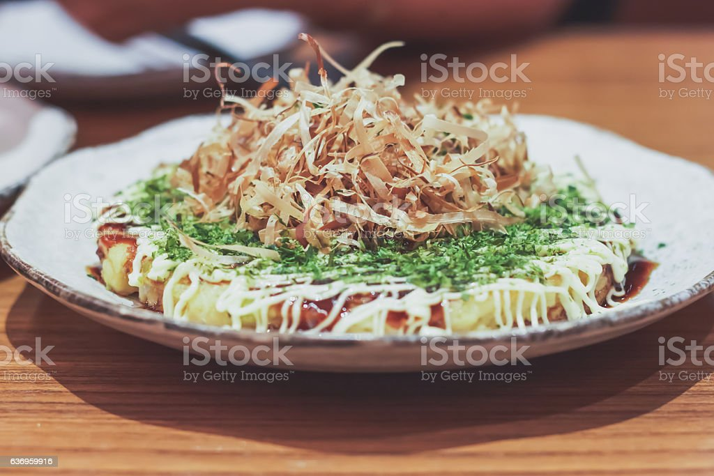 Japanese traditional food. Okonomiyaki or Japanese pizza in Japanese restaurant. stock photo