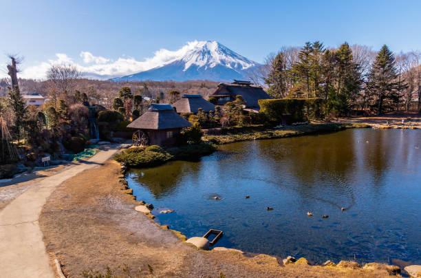 富士山を背景にしたおしの八海村の日本の伝統的な家屋。 - yamanaka lake ストックフォトと画像