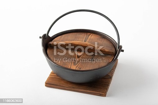 japanese traditional iron pot with wooden lid on white background