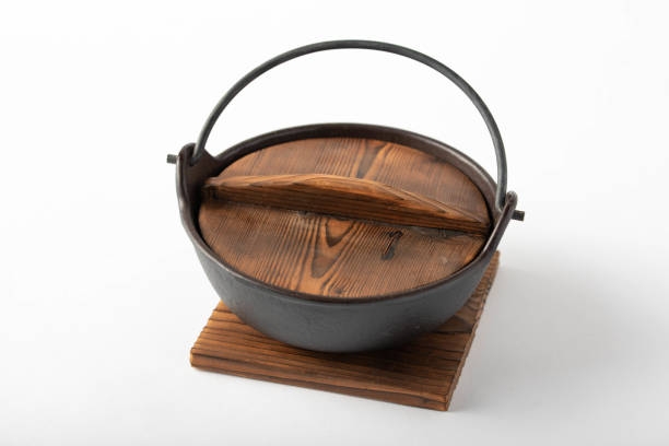 japanese traditional iron pot with wooden lid on white background stock photo