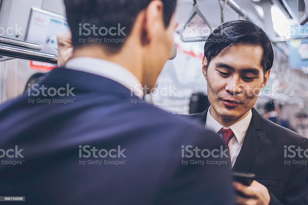 Asian Ethnicity businessmen travelling in the metro.