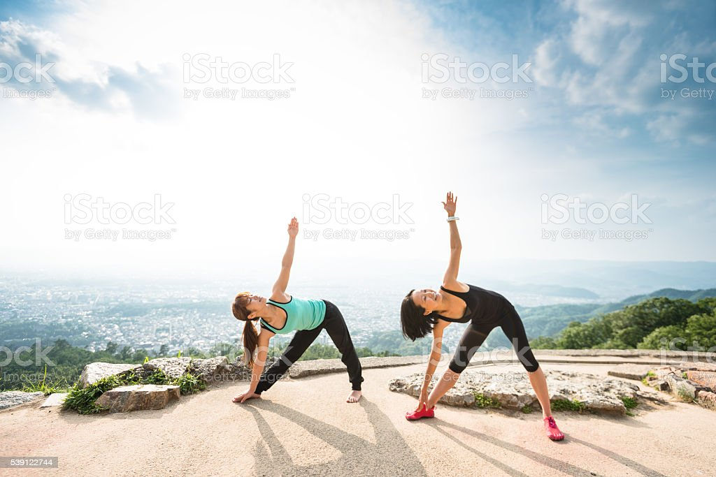 japanese woman doing yoga outdoors stock photo