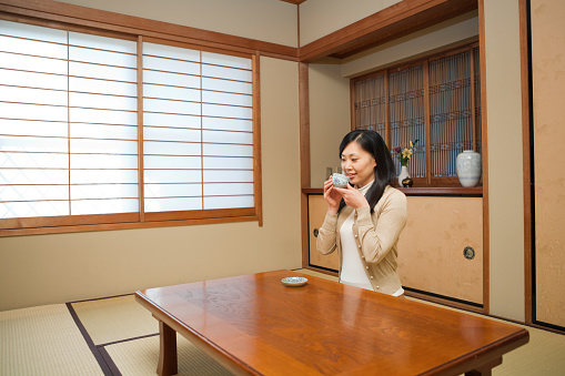 Japanese Woman Drinking Tea in Traditional Home
