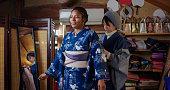 Japanese woman helping a tourist to put on a kimono. Okayama, Japan