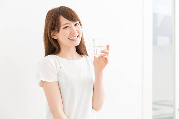 Japanese woman holding a glass of water ストックフォト