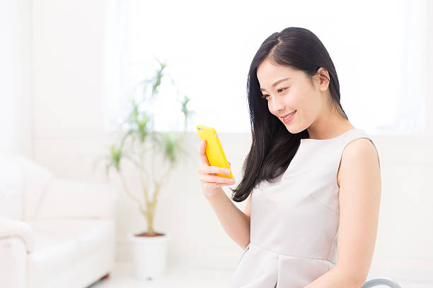 japanese woman holding a smart phone in a living room - スマホ 女性 ストックフォトと画像