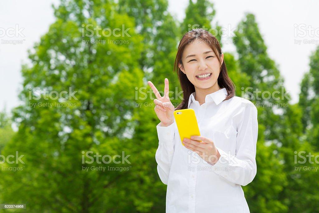 Japanese woman holding a smart phone zbiór zdjęć royalty-free