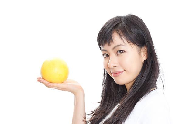 japanese woman holding an grapefruit - グレープフルーツ ストックフォトと画像