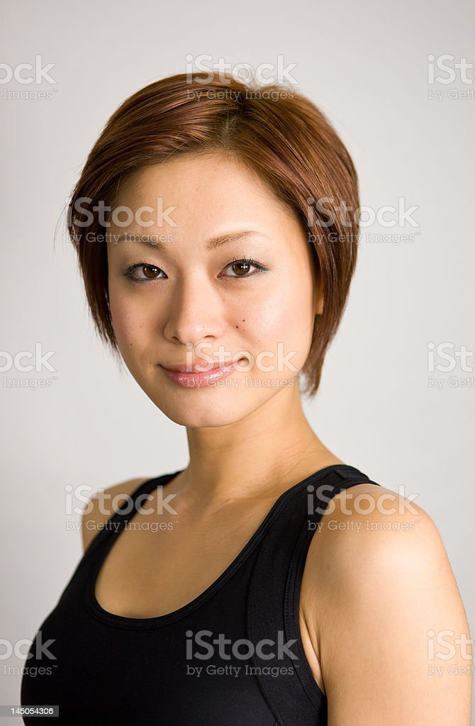 Japanese woman in a tank top A young Japanese woman poses in a black exercise tank top. 20-24 Years Stock Photo