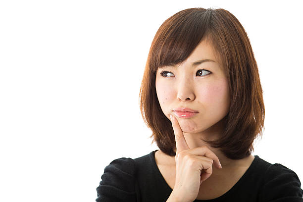 Japanese Woman in Doubt Young Asian woman looking skeptical. pink nail polish stock pictures, royalty-free photos & images