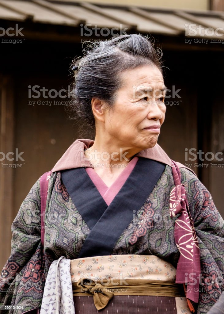 A senior aged Japanese woman standing on a dirt street in an Edo...