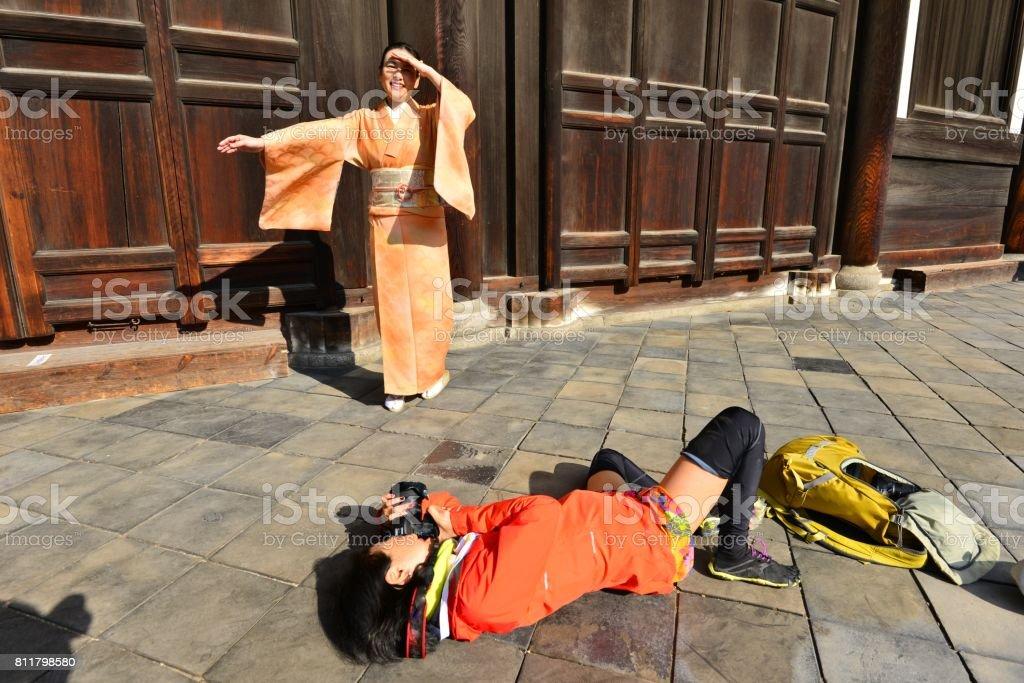 Japanese Woman in Kimono and Camerawoman at Tofuku-ji Temple, Kyoto stock photo