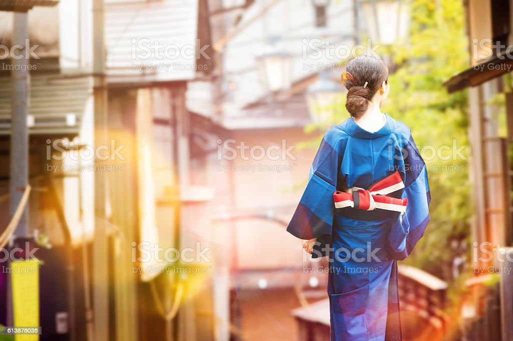 Japanese woman in kimono walking in village at sunset stock photo