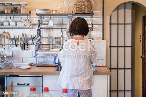 istock Japanese Woman in Modern Home Kitchen, Cooking and Washing Dishes 540232408