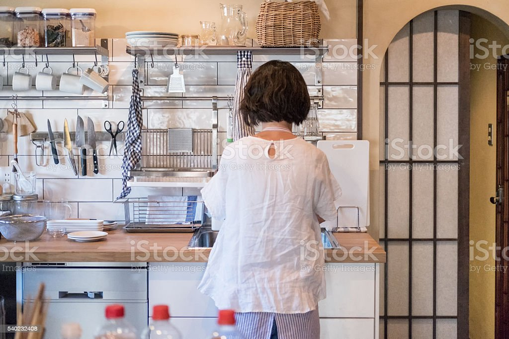 Japanese Woman in Modern Home Kitchen, Cooking and Washing Dishes stock photo