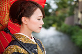 Japanese woman in traditional kimono holding an umbrella