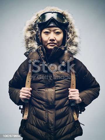 A Japanese woman wearing cold weather clothing including parka and goggles.