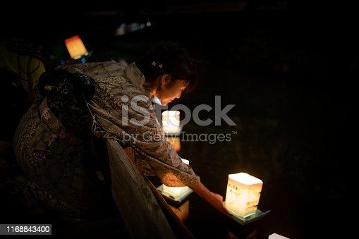 Japanese woman in yukata releasing paper lantern for toro nagashi event in summer Japan