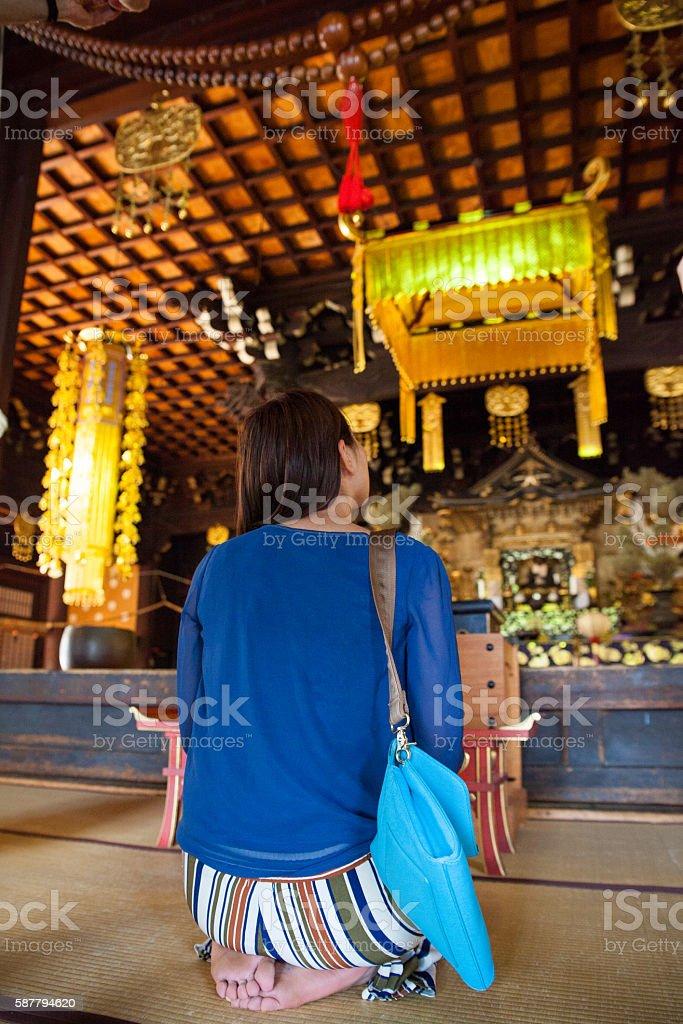 Japanese woman inside a buddhist temple - foto de acervo