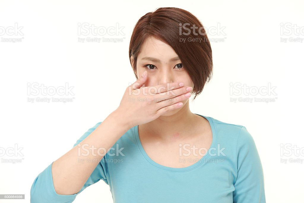 Japanese woman making the speak no evil gesture stock photo