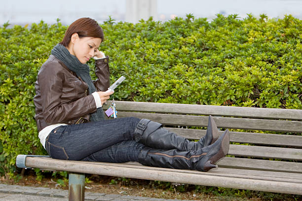 Japanese woman on a park bench stock photo