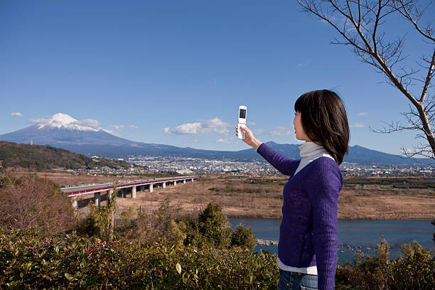 Japanese woman photographing Mt. Fuji stock photo