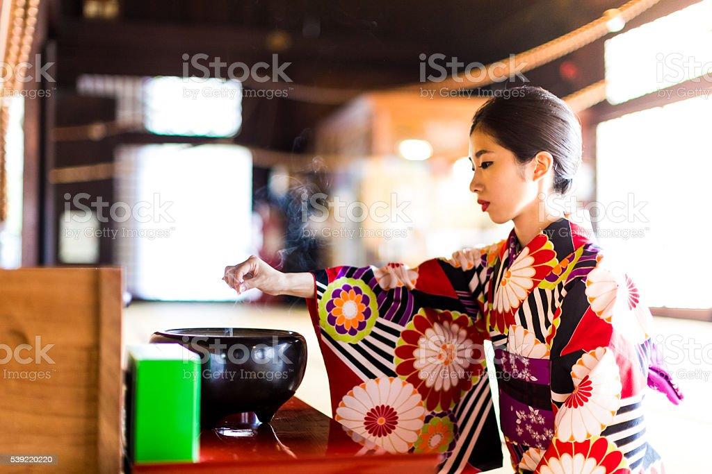 Japanese woman praying at the Hyakumanben Chionji Temple, Kyoto, Japan stock photo