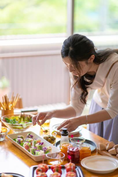 japanerin, vorbereitung für mittagessen party - oliven wohnzimmer stock-fotos und bilder