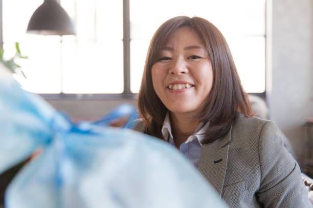 japanische frau empfangen vorhanden - geburtstagsgeschenke für beste freundin stock-fotos und bilder