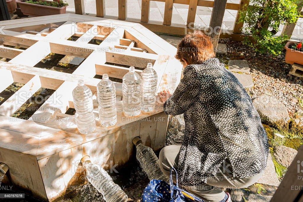 Japanese Woman Refills Water Bottles at Genchi Well Matsumoto Japan stock photo