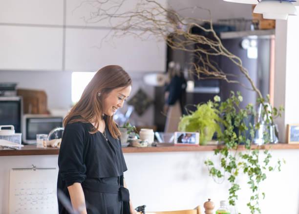 明るいダイニングルームでくつろぐ日本人女性 - sustainability ストックフォトと画像
