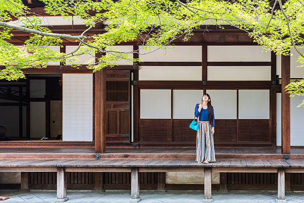 japanese woman relaxing in the grounds of buddhist temple - 寺院 ストックフォトと画像