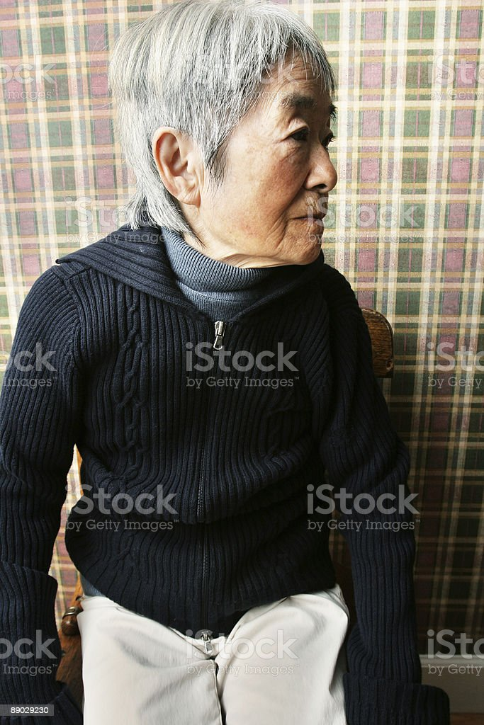 Japanese Woman Sitting Against Plaid Wall royalty-free stock photo