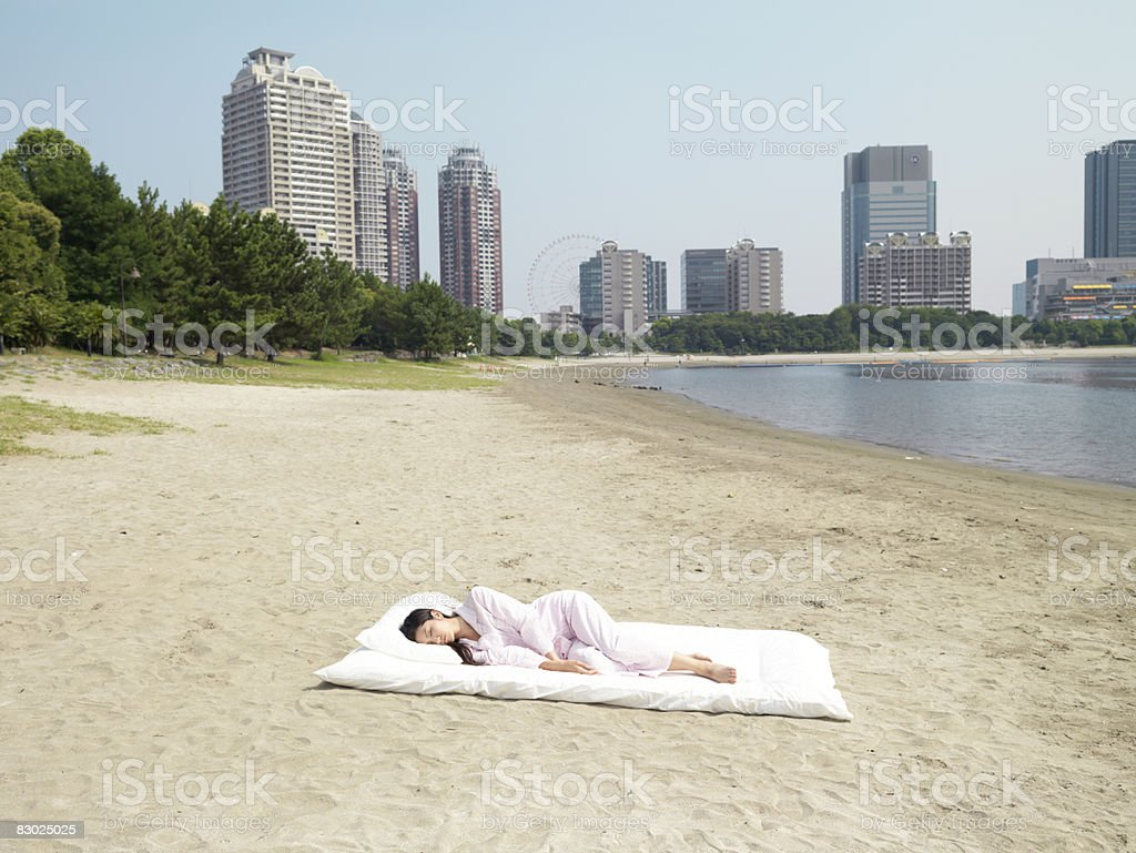 Japanese woman sleeping on futon, at beach royaltyfri bildbanksbilder