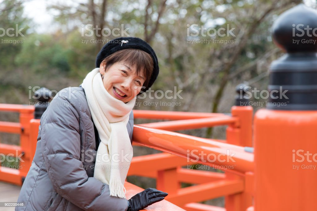 Japanese woman smiling on a red bridge stock photo