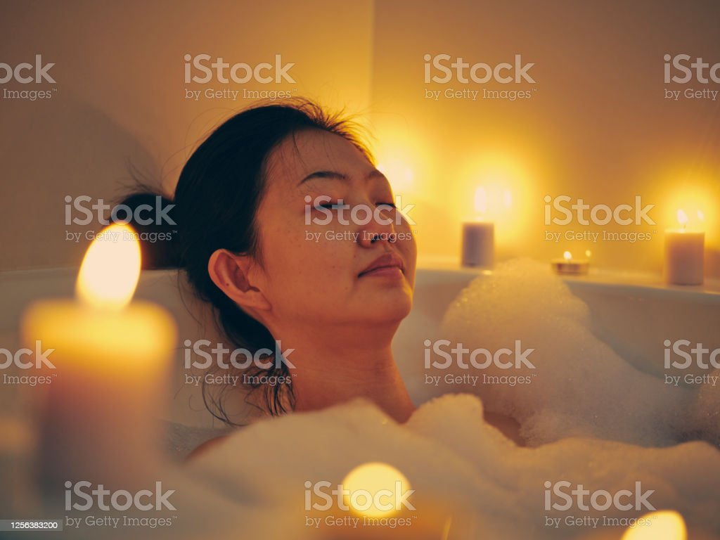 Japanese Woman Taking a Candlelight Bath A young Japanese woman relaxing in a bathtub, surrounded by candles. 30-39 Years Stock Photo