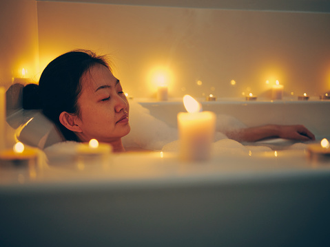 A young Japanese woman relaxing in a bathtub, surrounded by candles.