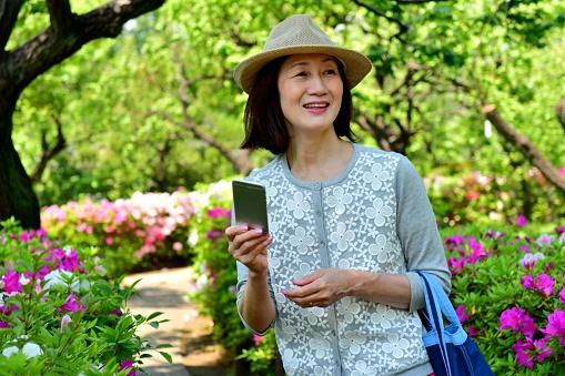 Japanese Woman Taking Selfie in Park with Azalea in Full Bloom