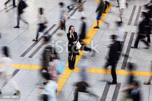 istock Japanese woman talking on the mobile phone surrounded by commuters 538676602