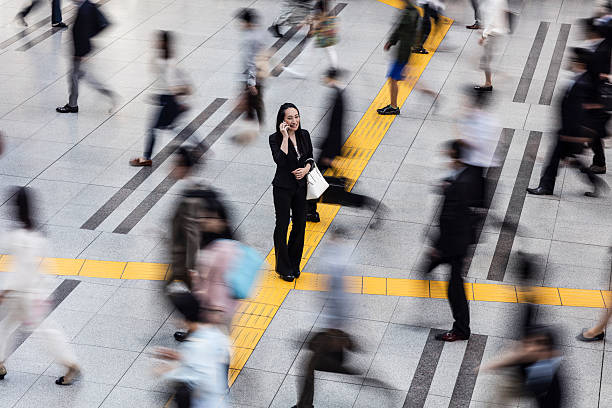 japanese woman talking on the mobile phone surrounded by commuters - international moving stock photos and pictures